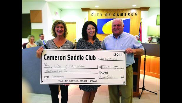 Photo by Annette Bauer Nina and Mark Baker present Mayor Darlene Breckenridge with a check for $1,000 from the Cameron Saddle Club.
