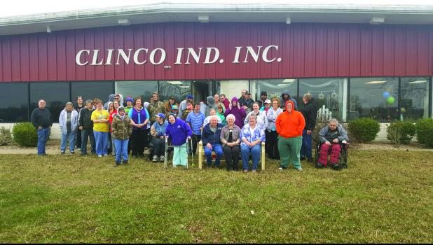 Clemons, seated in the middle, is pictured with Clinco administration and employees.