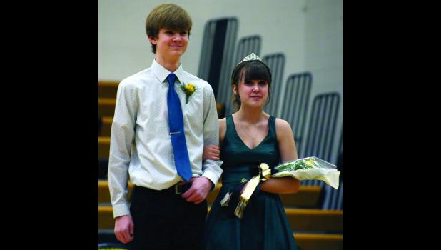 Freshman Graden Hammond escorts fellow attendant Allora Hurst Monday during the ceremony.