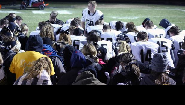 Cameron linebacker Camren Hedgpeth leads players, students and fans in a moment of silence.