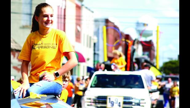 Cameron soccer manager Amelia Welch rides atop her father's truck Friday.