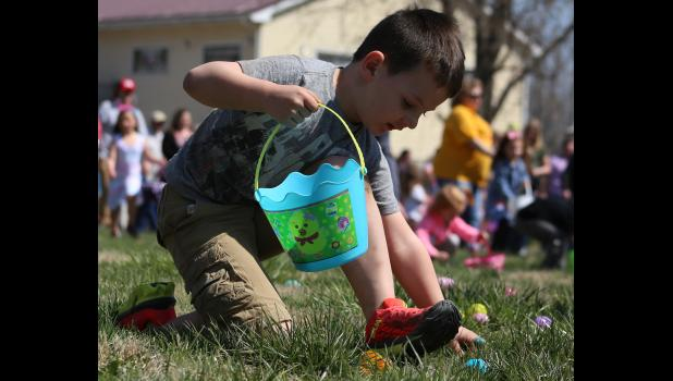 Maxton McKinley scoops up an egg Saturday afternoon.