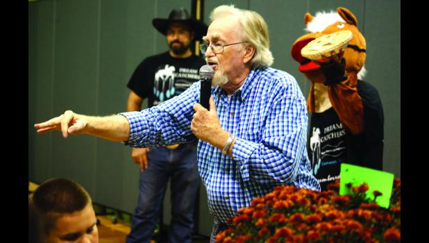 Clinton County Commissioner Larry King leads a dessert auction Saturday night.