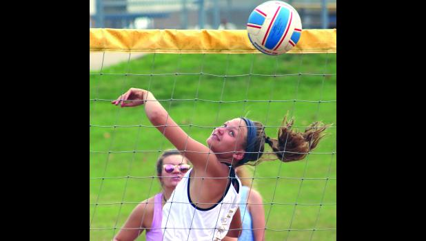 Cameron High School outside hitter Avery McVicker watches a shot go over the net during a special sand volleyball scrimmage Tuesday morning