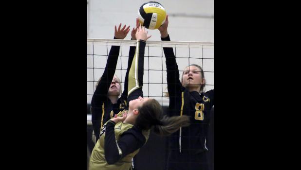 Lauren Burkhead and Avery McVicker block a shot at the net Saturday.