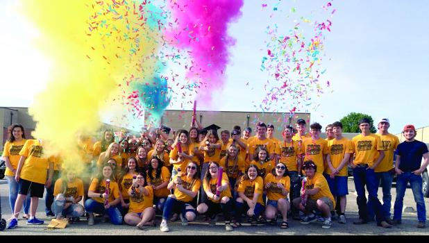 Cameron High School Class of 2020 seniors celebrate with smoke and confetti while posing for a photo following last Friday's senior parade