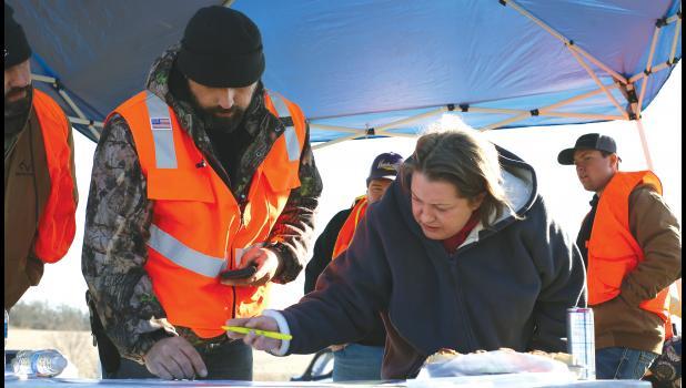 Search organizer Travis Eldredge reviews a map with landowner Brenda Northon Sunday afternoon.
