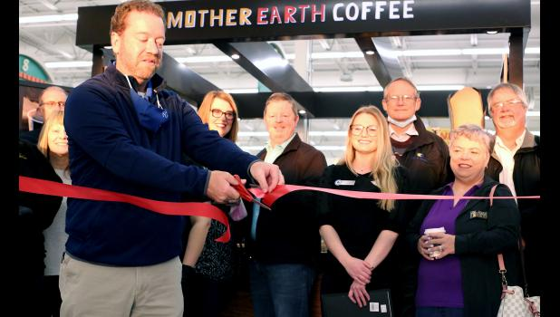 Cameron Market Owner Tony Clark cuts the ribbon on the recently opened Mother Earth Coffee kiosk.