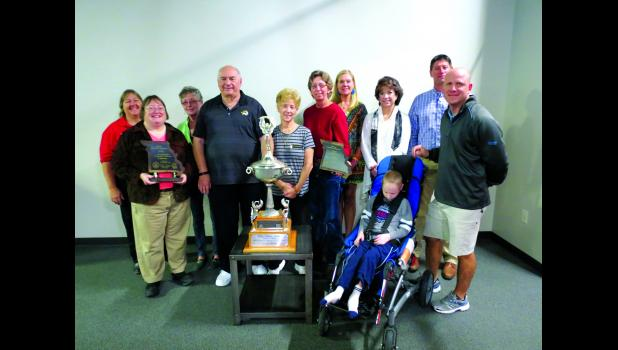 Mary Jo Eiberger, Gina Reed, Pat Jones, Jack Briggs, Alene Briggs, Dr. Nada Woodworth, Mary Murdock, Becky Curtis, Drew Bontrager, Aiden McVicker and Jamey McVicker pose with the the Missouri Community Betterment trophy and plaque. The trophy will be on display at the YMCA through the month of November.