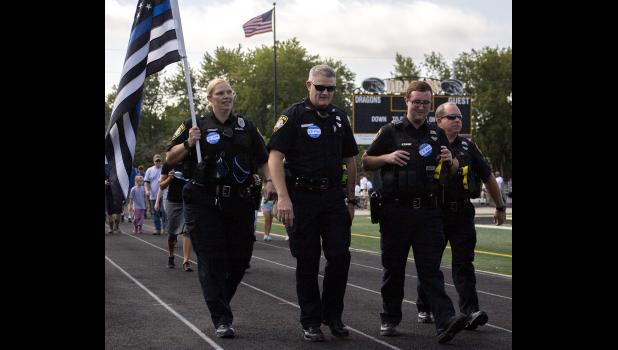 Members of the Cameron Police Department march with participants of Saturday's Out of Darkness Suicide Awareness Walk.