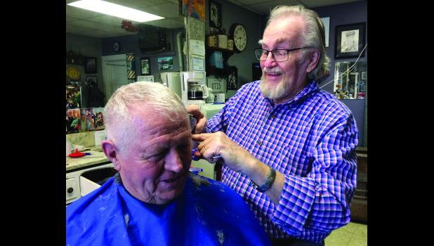 King's Barber Shop Owner Larry King trims customer Bill Stocklas' hair Saturday morning in Cameron.