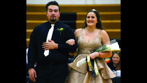 Jesse Flores escorts fellow senior candidate Aubrey Brown.