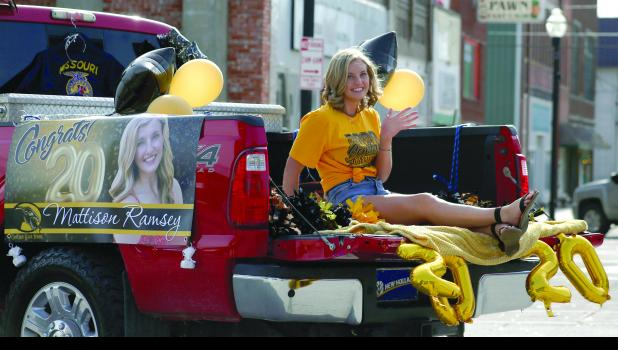 Mattison Ramsey rides through downtown in an adorned truck bed.