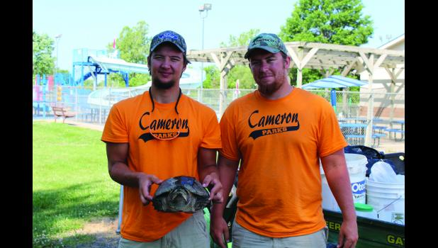 Marshall Colson (left)  and Mitchell Colson (right) hold the snapping turtle found in the Cameron pool.