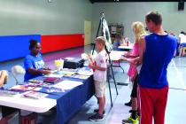 Representatives from MoDot talk to kids about the importance of seat belt safety during the CAP Annual Back to School Fair at the YMCA.