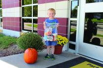 Pre-school student, Xavier Copple, happily holds a Second Harvest Backpack complete with non-perishable, healthy food choices.
