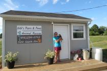 Georgia Drager and her cat Lisle in front of the new home of Gigi's Purrs and Pawz Animal Rescue.