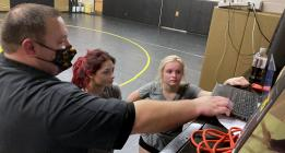 Coach Phil Limnb and wrestlers Ashley Yamat and Christina Herring check out the district competition.