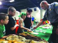 Brittany Wood, Caelen Bracken, Riley Wood, Kaine Wood get a lesson on pelts and wild animal footprints from Missouri Conservation Department District Supervisor J.M. Braunecker Thursday morning.