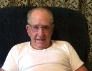 Vernon relaxes in his Cameron home with a large photo album full of military memories.