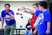 Science City Educator Jordan Fox has kids drop racket balls at differing heights to demonstrate the rate of speed in which they will hit the ground.
