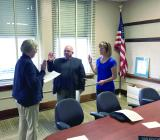 Board Secretary Carmen Kerr, left, swears in newly elected Dan Kercher, center, and Jackie Peck, right, to begin their terms on the Cameron R-I School Board.