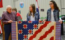 """Army Veteran Jim Findley of Osborn being presented with a """"Quilt of Valor"""" by Mackenzie Perry and Abby Hall on behalf of Carol Boothe, quilter at the Osborn Veterans Day Assembly."""