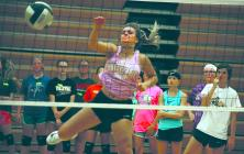 Cameron High School setter Aly Yates shows campers how to hit Tuesday night.