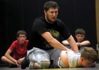 Assistant Wrestling Coach Zach Black works on pins last Thursday night.